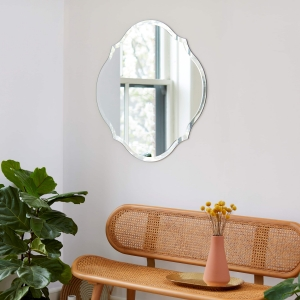 Frameless scalloped round mirror hanging on wall above bench and plant