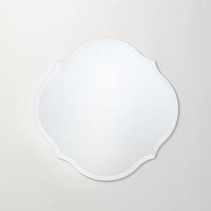 Frameless scalloped round mirror hanging on beige wall
