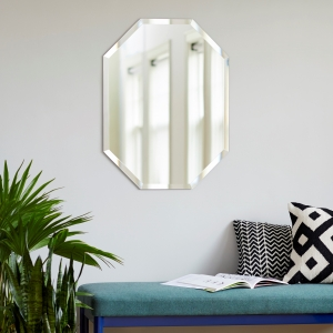 Frameless beveled octagon mirror on wall over a bench